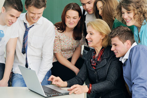 Smiling teacher with a group of happy students looking at a laptop