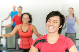 Smiling woman at fitness class gym workout on treadmill