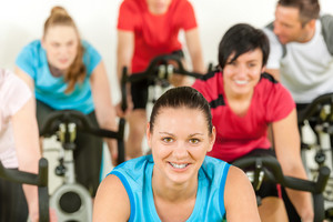 Smiling woman at spinning class fitness workout people exercise