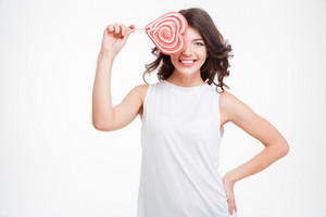 Smiling woman covering eye with lollipop isolated on a white background