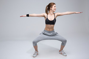Smiling woman doing stretching excersises over gray background