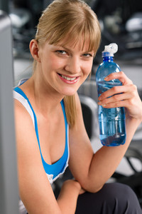 Smiling woman drink water relax at weight machine fitness center