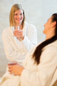 Smiling woman drinking water with friend at beauty spa