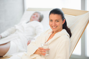 Smiling woman hold glass of water at beauty spa