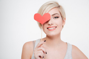 Smiling woman holding red heart isolated on a white background