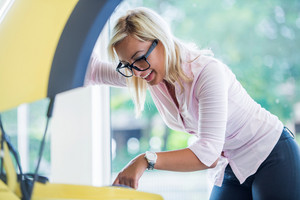 Smiling woman looking under yellow car hood