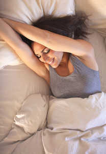 Smiling woman lying on bed wakes up to a beautiful morning