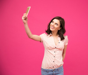 Smiling woman making selfie photo on smartphone