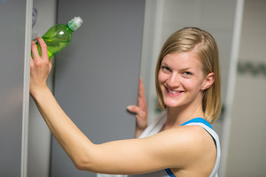 Smiling woman putting water bottle in locker at healthclub