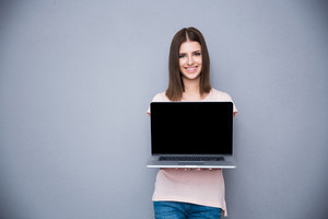 Smiling woman showing blank laptop computer screen
