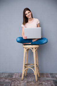 Smiling woman sitting on the chair with laptop