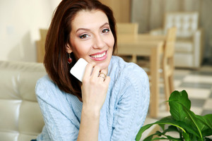 Smiling woman sitting on the sofa and holding smartphone at home