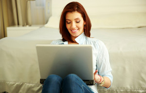 Smiling woman sitting with laptop at home