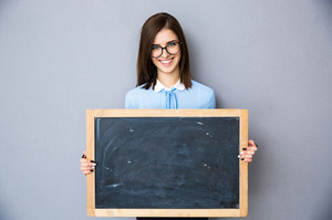 Smiling woman standing with billboard over gray background. Wearing in blue shirt and glasses. Looking at camera