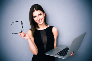 Smiling woman standing with laptop and glasses