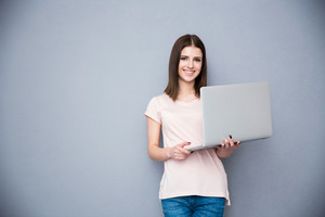 Smiling woman standing with laptop over gray background