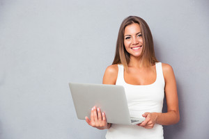 Smiling woman standing with laptop
