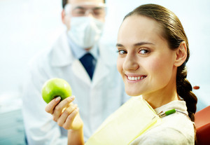 Smiling woman with apple looking at camera with dentist on background