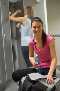 Smiling woman with friend in background at gym's locker room