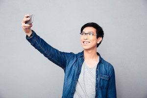 Smiling young asian man making selfie photo
