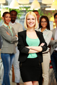 Smiling young businesswoman standing in front of colleagues at office