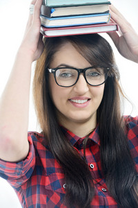 Smiling young caucasian girl with glases and a checkered shirt isolated on white holding a pile of books on her head