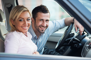Smiling young couple posing sitting in a car