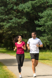 Smiling young couple running in park
