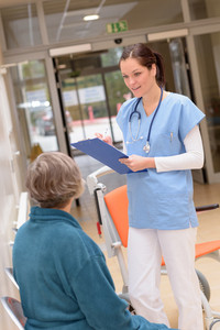 Smiling young female doctor in hospital talking to senior patient in hospital