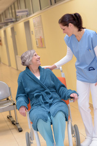Smiling young female doctor in hospital talking to senior patient in wheelchair