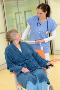 Smiling young female nurse in hospital looking at senior patient in wheelchair in hospital