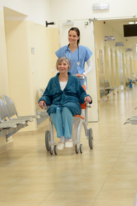Smiling young female nurse in hospital pushing senior patient in wheelchair in hospital corridor