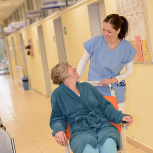 Smiling young female nurse in hospital taking care of senior patient in wheelchair