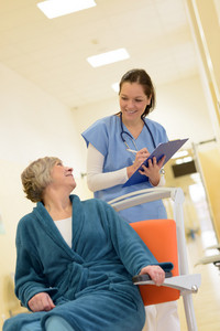Smiling young female nurse watch senior patient in hospital while holding her files