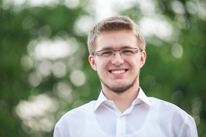 Smiling young man with glasses on bokeh background