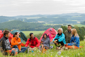 Smiling young people enjoying nature beside tents and scenic view