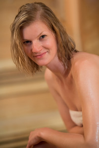 Smiling young woman in sauna