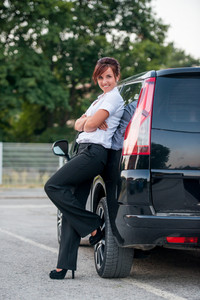 Smiling young woman leaning on a car posing