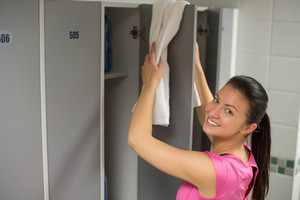 Smiling young woman placing towel on locker door at gym
