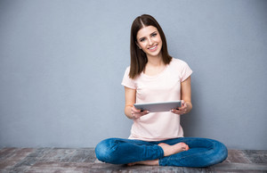 Smiling young woman sitting on the floor with tablet computer