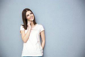 Smiling young woman talking on the phone over gray background