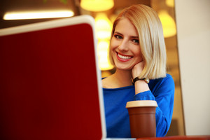 Smiling young woman using laptop and looking at camera