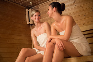 Smiling young women talking while relaxing in sauna