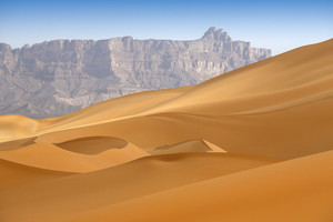 Smooth desert sand dunes and a rocky mountain cliff