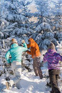 Snowball fight winter friends having fun playing in snow outdoors
