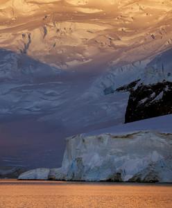 Snowy coast and iceberg at sunset