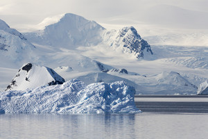 Snowy coast and iceberg in still waters