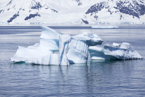 Snowy coast and sunlit iceberg
