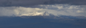 Snowy mountain peak under a stormy sky