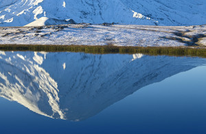 Snowy mountain reflected in a smooth lake